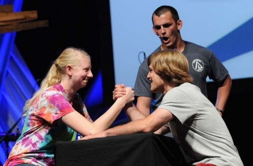 Shelley West arm-wrestles fellow Youth Peace Travel Team member Chris Bache at National Youth Conference . Photo by Glenn Riegel
