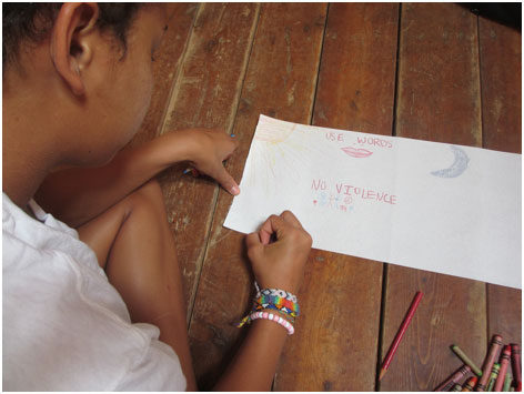 "Child drawing the words ""No violence"" at Camp Koinonia"