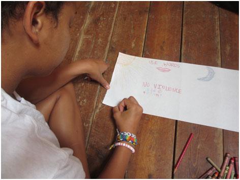 """Child drawing the words """"No violence"""" at Camp Koinonia"""
