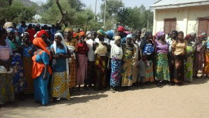 Women wait in line to receive food supplies.