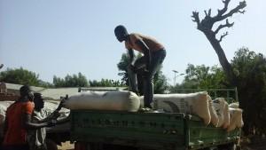 Relief workers unload bags of grain.